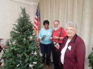 Cornwall Manor residents (fro left to right) Debbie and Steve Grubbs and Mary Jones select stars off the Christmas tree at the November Cornwall Manor Society meeting.