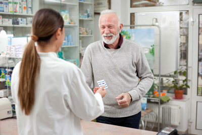 A pharmacist is handing a smiling man a prescription at the pharmacy