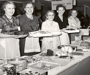 Five ladies holding various baking dishes, such as cake and donuts